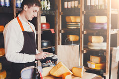 Male cheese shop assistant swipe credit card. Retail, credit card payment service. Male shop assistant conducts a payment with credit card for order of cheese in Stock Images