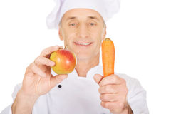 Male chef with an apple and carrot Stock Images