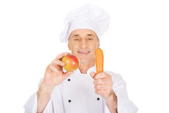 Male chef with an apple and carrot Stock Photos
