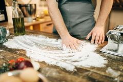 Chef in apron, flour,eggs, pasta machine on table. Male chef in apron, flour,eggs and pasta machine on wooden table. Ingredients for homemade spaghetti Stock Image