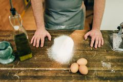 Male chef in apron, flour and eggs on wooden table. Homemade pasta cooking Royalty Free Stock Photos
