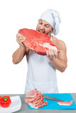 Male chef bodybuilder eats raw meat. Royalty Free Stock Photo