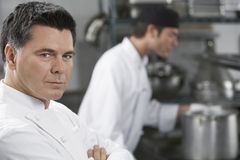 Male Chef With Colleague In Kitchen Royalty Free Stock Image