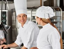Male Chef With Colleague At Kitchen Stock Image