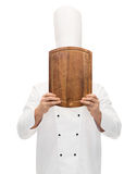 Male chef cook covering face with cutting board Stock Images