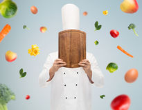 Male chef cook covering face with cutting board. Cooking, profession and people concept - male chef cook covering face or hiding behind wooden cutting board over stock photo