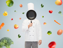 Male chef cook covering face with frying pan Stock Photo