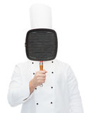 Male chef cook covering face with grill pan Stock Photo