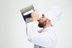 Male chef cook drinking from pot. Portrait of a male chef cook drinking from pot isolated on a white background Stock Photos