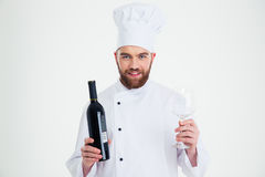 Male chef cook holding bottle of wine and wineglass i Royalty Free Stock Image