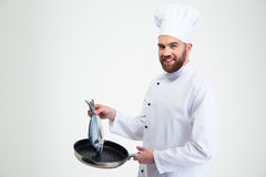 Male chef cook holding pan with fish Royalty Free Stock Images