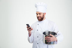 Male chef cook holding pot and using smartphone. Portrait of a happy male chef cook holding pot and using smartphone  on a white background Stock Photo