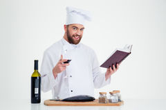 Male chef cook holding recipe book and glass with red wine Royalty Free Stock Photos