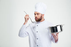 Male chef cook holding a saucepan and ladle Royalty Free Stock Images
