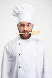 Male chef cook holding spoon in teeth. Portrait of a handsome male chef cook holding spoon in teeth isolated on a white background Royalty Free Stock Photography