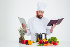 Male chef cook holding tablet computer and receipe boo Royalty Free Stock Photo