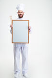 Male chef cook iun uniform holding blank board. Full length portrait of a cheerful male chef cook iun uniform holding blank board isolated on a white background Royalty Free Stock Image