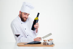 Male chef cook preparing fish and holding bottle with red wine Royalty Free Stock Photography