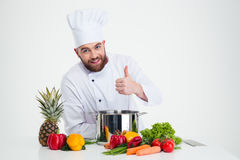 Male chef cook preparing food and showing thumb up. Portrait of a happy male chef cook preparing food and showing thumb up isolated on a white background Royalty Free Stock Photo