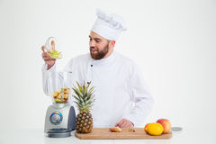 Male chef cook using blender with fruits Royalty Free Stock Photo