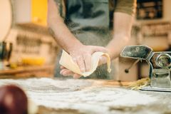 Male chef cooking dough and prepares pasta machine. Male chef in apron cooking dough and prepares pasta machine on wooden kitchen table Stock Image