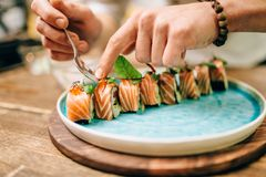 Male chef cooking sushi rolls, japanese food Stock Photography