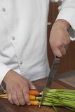 Male Chef Cutting Carrots On Wooden Board Stock Photo