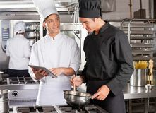 Male Chef Assisting Colleague In Preparing Food Stock Photography
