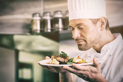 Male chef with eyes closed smelling gourmet food. Closeup of a male chef with eyes closed smelling gourmet food in the kitchen stock photos
