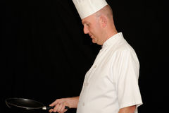 Male chef with frying pan. A male chef standing and holding a frying pan in the kitchen Royalty Free Stock Image