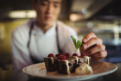 Male chef garnishing dessert plate Royalty Free Stock Images