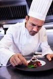 Male chef garnishing dessert plate stock photos