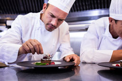 Male chef garnishing dessert plate royalty free stock photography