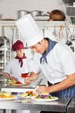 Male Chef Garnishing Dish. Young male chef garnishing dish with female colleague in background Stock Photography