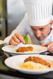 Male chef garnishing food in kitchen Royalty Free Stock Photos
