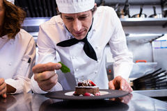Male chef garnishing his dessert with a mint leaf on counter. In commercial kitchen Stock Image