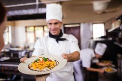 Male chef giving plate of prepared food to waitress in kitchen royalty free stock photos