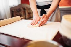 Male chef hands and dough, strudel cooking. Male chef hands and dough on wooden table. Homemade strudel cooking Royalty Free Stock Image
