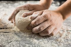Male chef hands knead dough with flour on kitchen table. Side view stock photography