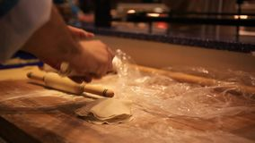 Male chef hands preparing dough with rolling pin stock video footage