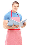A male chef holding a cookbook and looking at camera Stock Photography
