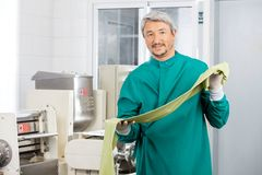 Male Chef Holding Green Spaghetti Pasta Sheet By Stock Image