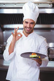 Male chef holding plate and doing ok sign Royalty Free Stock Image