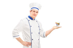 Male chef holding a small shopping cart with food products. Isolated on white background Stock Photo