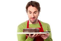 Male chef holding yummy chocolate cake. Young chef staring at chocolate cake while holding it Stock Image
