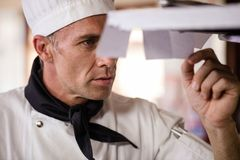 Male chef looking at order list in kitchen royalty free stock photos