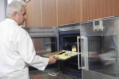 Male Chef Placing Baking Tray In Oven. Side view of male chef placing baking tray in oven royalty free stock photo