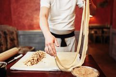Male chef prepares dough for apple strudel. On wooden kitchen table, pastry preparation process. Homemade sweet dessert Stock Images