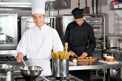 Male Chef Preparing Food. With colleague chopping carrot in industrial kitchen royalty free stock photo