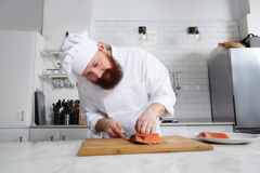 Male chef preparing gourmet meal of seafood in modern kitchen Stock Photography